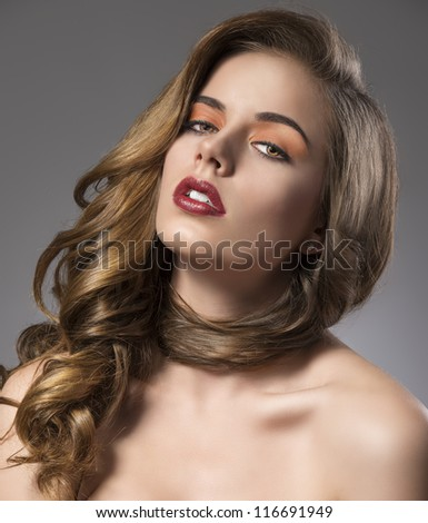 beautiful woman with long wavy hair and dark dress, her face is relieved and she looks in to the lens - stock photo