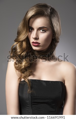 beautiful woman with long wavy hair and dark dress, her face is turned of three quarters at right and looks in to the lens - stock photo