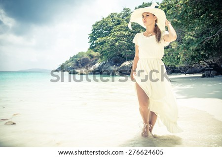 Beautiful woman with long white dress and hat walking on a tropical beach with crystalline water - Fashion model in a idyllic vacation resort - stock photo