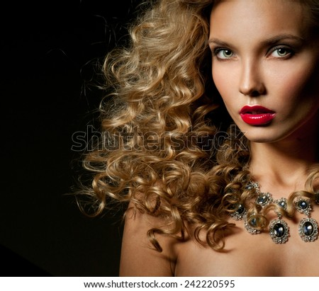 Beautiful woman with magnificent curly hair. Red lipstick. Necklace. - stock photo