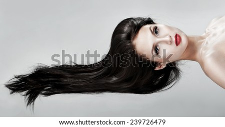 Beautiful woman with magnificent hair. Flying hair. Red lipstick. - stock photo