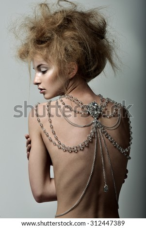 Beautiful woman with magnificent hairstyle. Great decoration on the back, body Chain - stock photo