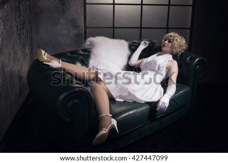 Beautiful woman with make-up skeleton lying on the sofa in a dark gothic interior
