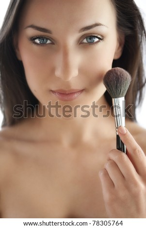 Beautiful woman with makeup brush near her face - isolated on white - stock photo