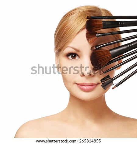 Beautiful woman with makeup brushes near attractive face, isolated on white