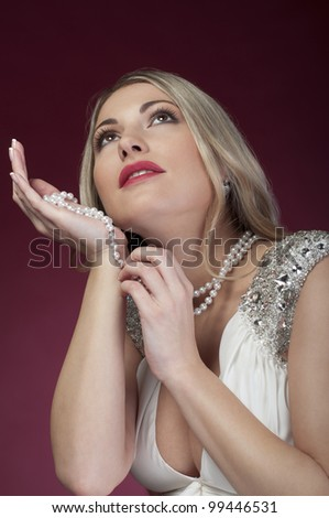 Beautiful woman with makeup holds perl beads - stock photo