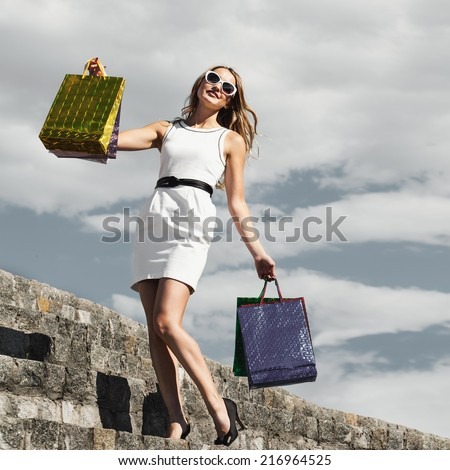 Beautiful woman with many shopping bags in city. Concept. Blonde sexy happy girl in street, outdoors - stock photo