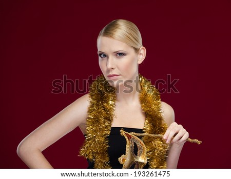 Beautiful woman with masquerade mask and tinsel, isolated on purple - stock photo