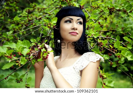 Beautiful woman with mulberry outdoors in summer