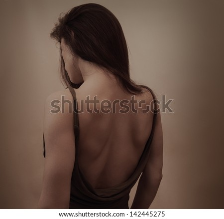 Beautiful woman with naked back in dress posing on dark background - stock photo
