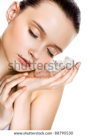 Beautiful woman with natural looking makeup holding ice cubes near face