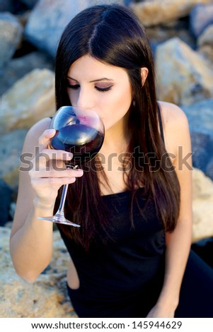Beautiful woman with night dress sitting on rocks smelling red wine - stock photo