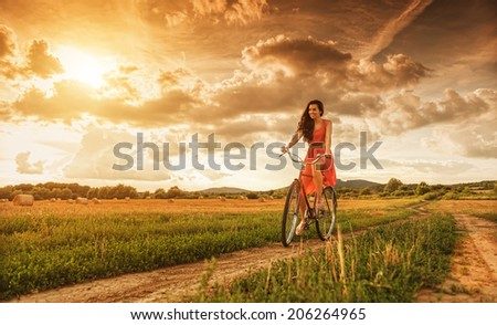 Beautiful woman with old bike in a wheat field  - stock photo