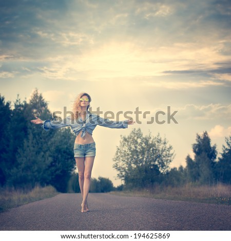 Beautiful Woman with Open Arms under the Sunrise Walking on the Country Road. Dramatic Sky. Instagram Styled Toned Photo. - stock photo