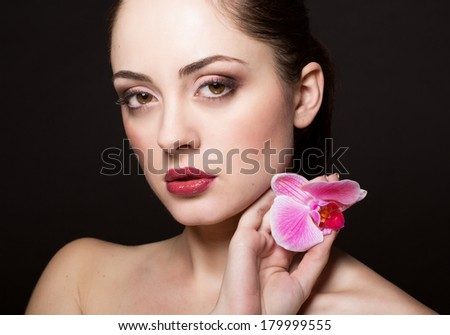 Beautiful woman with orchid - stock photo