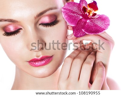 Beautiful woman with orchid in pink light - stock photo
