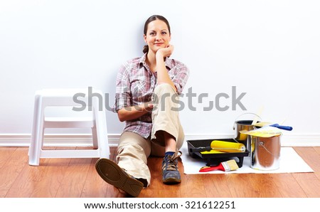Beautiful woman with painting roller. House renovation. - stock photo