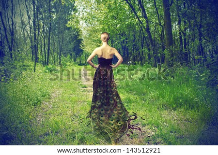 beautiful woman with peacock feather dress - stock photo