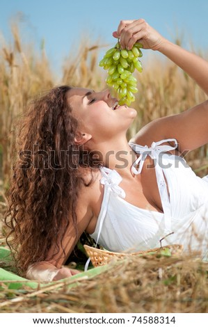 Beautiful woman with perfect hair and skin posing in wheat field and eating green grapes. Picnic.