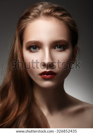 Beautiful woman with perfect skin and long hair on a grey background - stock photo