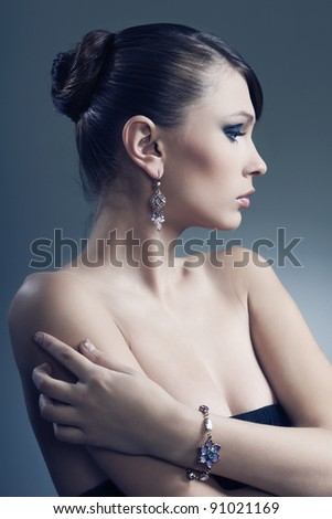 beautiful woman with perfect skin in black dress with jewelry - stock photo