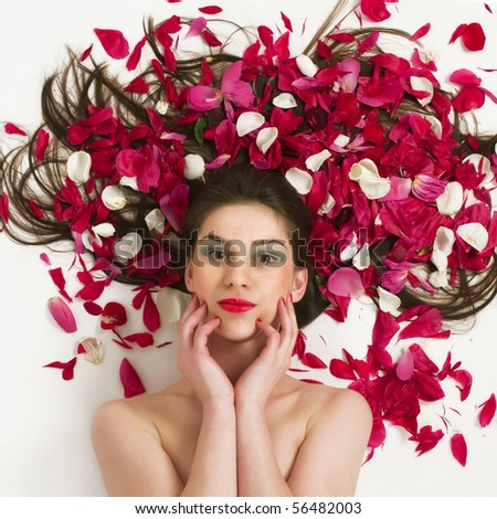 Beautiful woman with petal's of red roses above her long hair - stock photo