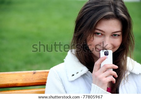 Beautiful woman with phone on the bench - stock photo