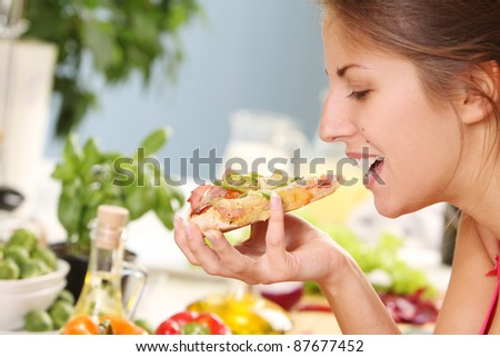 Beautiful woman with pizza on the kitchen - stock photo