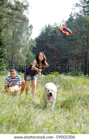 Beautiful woman with playful young dog. Frisbie - stock photo