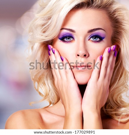 Beautiful  woman with purple nails  and bright glamour makeup - stock photo