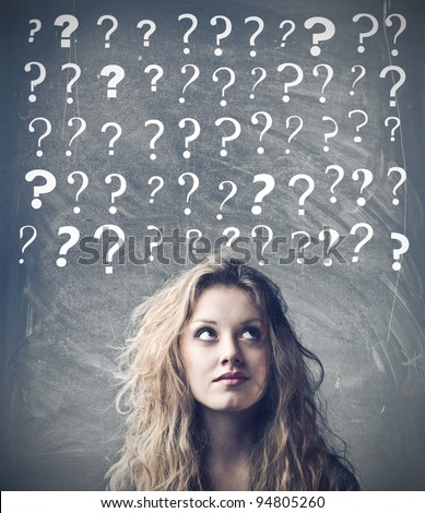 Beautiful woman with questioning expression and question marks above her head - stock photo