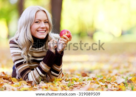 Beautiful woman with red apple in autumn park - stock photo