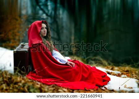 beautiful woman with red cloak in the woods, sitting on ground - stock photo