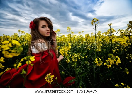 beautiful woman with red cloak on blooming rapeseed field in summer - stock photo