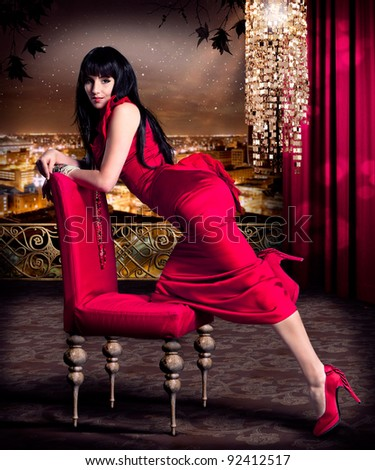 beautiful woman with red evening dress on a terrace with skyline of a city behind - stock photo