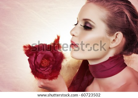 beautiful woman with red feather rose and bright make-up on pink background with copy space. - stock photo