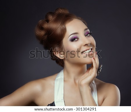 beautiful woman with red hair against dark studio background - stock photo