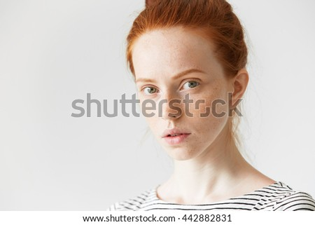 Beautiful woman with red hair and freckles wearing sailor shirt, looking at the camera with serious and concentrated expression, thinking of something, against white copy space wall for your content - stock photo