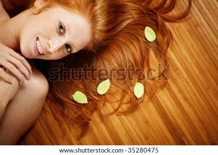 Beautiful woman with red hair and leaves on it lying on wooden floor in spa salon - stock photo