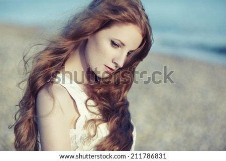 Beautiful woman with red hair at the sea. Fashion photo