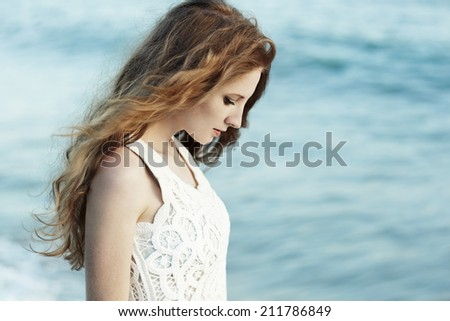 Beautiful woman with red hair at the sea. Fashion photo - stock photo