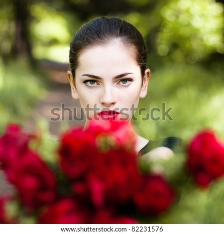 Beautiful woman with red lips giving flowers. Close up portrait - stock photo