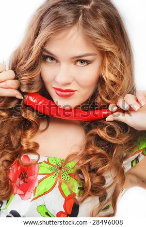 Beautiful woman with red lips holding chili pepper - stock photo