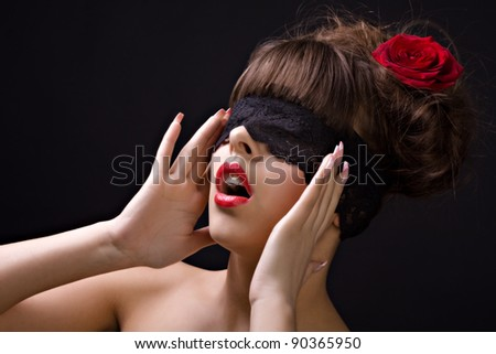 Beautiful woman with red rose in her hair and lace mask - stock photo
