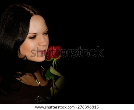 Beautiful woman with red rose on black background