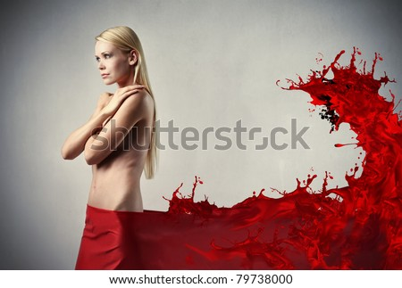 Beautiful woman with red tissue on her hips melting in red liquid - stock photo