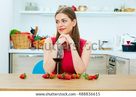 Beautiful woman with red wine glass sitting in kitchen with strawberry on table.