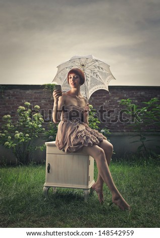 beautiful woman with romantic dress sitting in the garden writes on the phone - stock photo