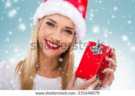 Beautiful woman with santa hat holding red gift box, close-up - stock photo