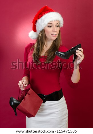 Beautiful woman with Santa Hat holding shoes on a red background - stock photo
